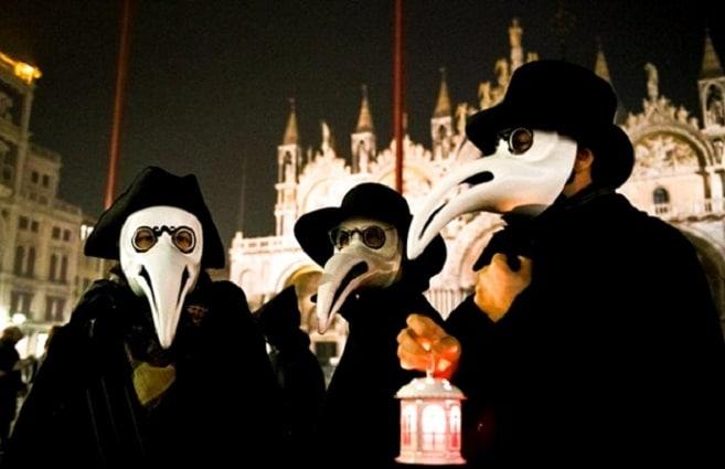 3 personas disfrazadas del médico de la peste durante el carnaval de venecia. Al fondo se puede ver la Basílica de San Marcos
