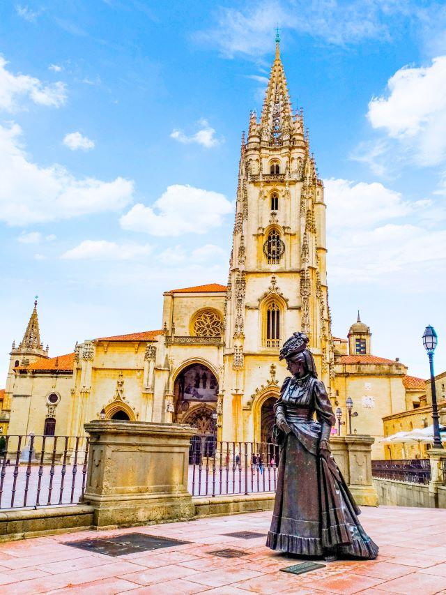 Estatua de la Regenta y al fondo la Catedral de oviedo, uno de los lugares imprescindibles que ver en oviedo en un día