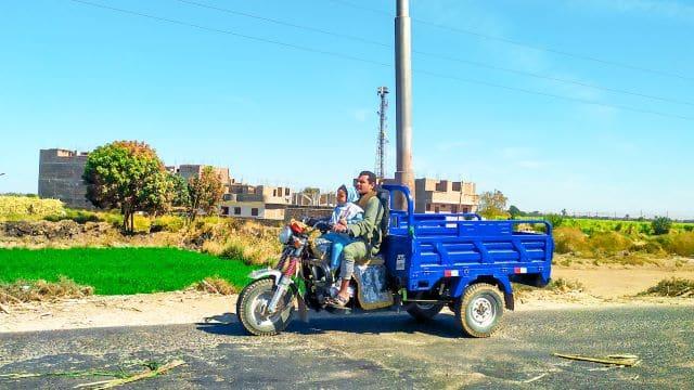 Un hombre con su hija en una moto carro