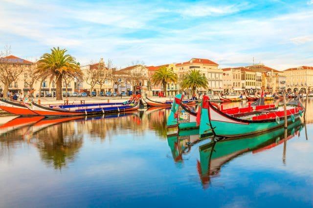 Típicos barcos moliceiros con Aveiro de fondo, una de las mejores ciudades que ver en los alrededores de Oporto