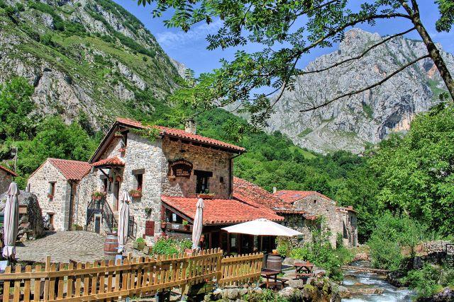 Arquitectura típica de Bulnes con los Picos de Europa de fondo, uno de los lugares imprescindibles que ver en el interior de Asturias